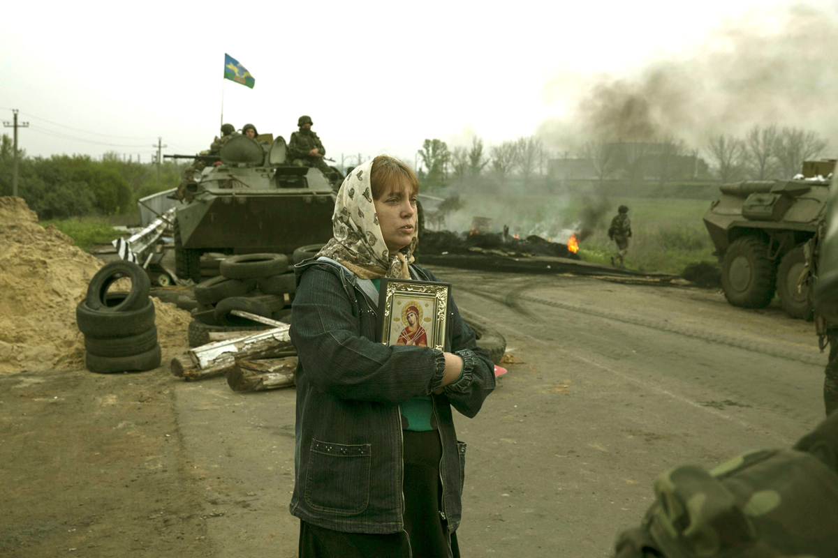 A woman stands with an Orthodox icon at a Ukrainian checkpoint near the town of Slaviansk in eastern Ukraine May 2, 2014. Ukrainian forces attacked the rebel-held city of Slaviansk before dawn on Friday and pro-Russia separatists shot down at least one attack helicopter, killing a pilot, in a sharp escalation of the conflict. REUTERS/Baz Ratner (UKRAINE - Tags: POLITICS CIVIL UNREST RELIGION TPX IMAGES OF THE DAY)